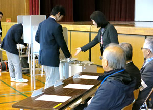 笑顔の説明を受けながら投票、立会人の視線も気付いています